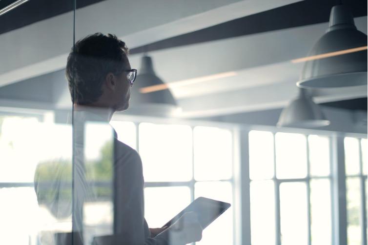 Man looking through office door